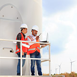 Engineers working at wind turbine power generator station installation site